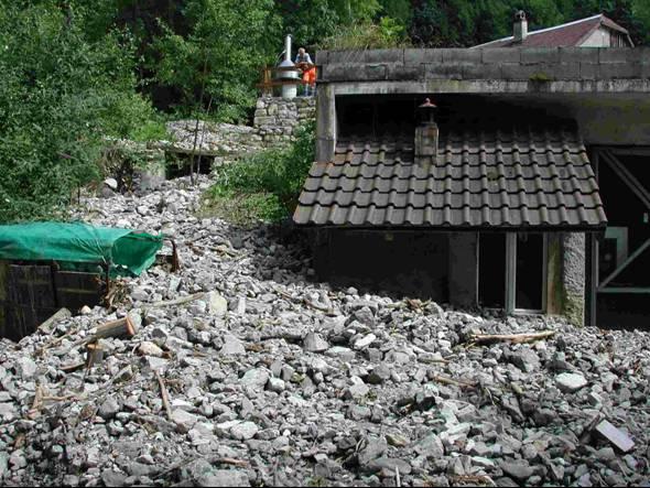 Dépôt de lave torrentielle et dégâts aux constructions.