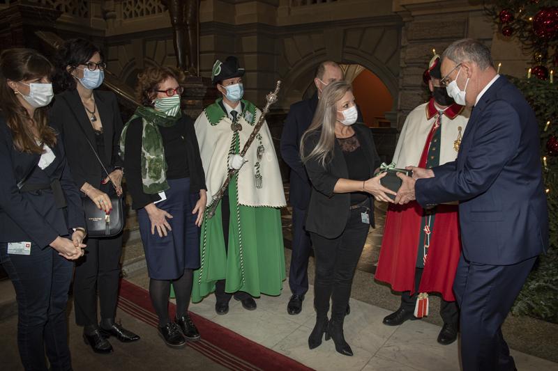 Le présidente du Conseil d'Etat Nuria Gorrite tend une boîte entourée d'un ruban au nouveau président de la Confédération.