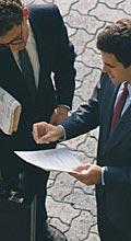 Sur une place publique, deux hommes d'affaires examinent un document écrit